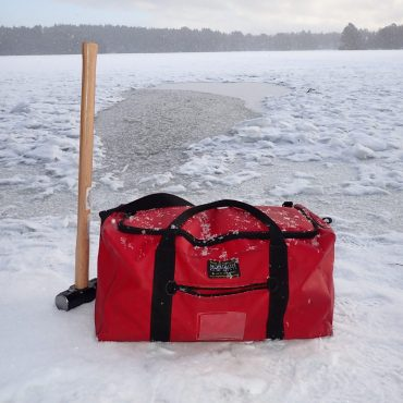 Image shows a red Montrose Bag on ice, with a hammer for outdoor swimming.